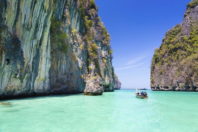 Dramatiske klipper omkranser lysende turkist havvand. En lille båd sejler i solen.