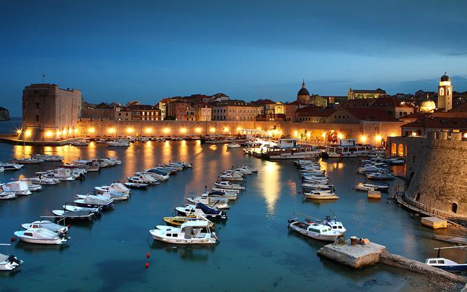 The port of Dubrovnik lit up at dusk.