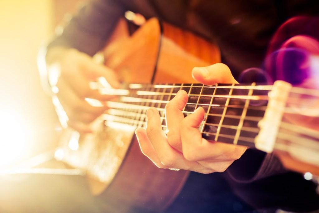 Κιθαρίστας ατμοσφαιρικά φωτισμένος - παρακολουθήστε συναυλίες κλασική μουσικής στο Φεστιβάλ Νάξου