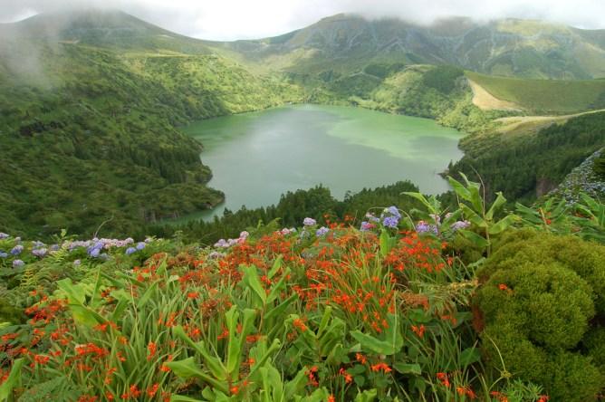 Λίμνη περιτριγυρισμένη από πράσινους λόφους με λουλούδια στις Αζόρες