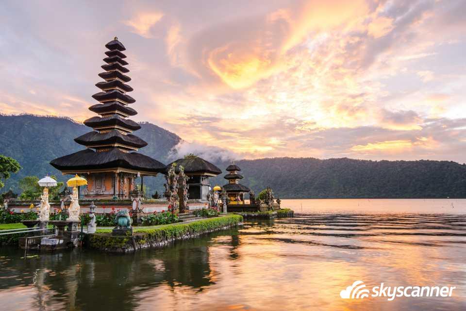 Tempel i solnedgang. Templet er spidst, og ligger ud til vand. Himlen er rød af solnedgang.
