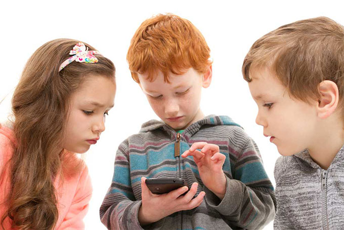 Three children looking at a calculator