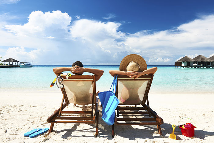 Couple relaxing on the beach. Black Friday Cyber Monday flight deals.