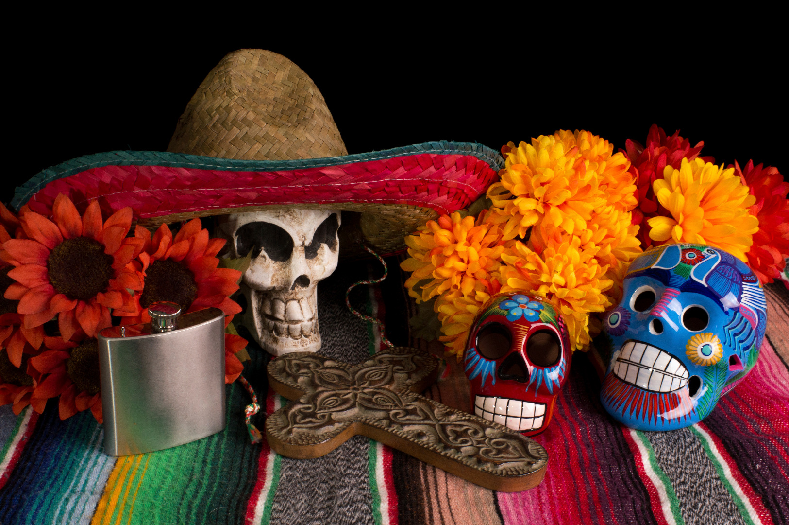 A Day of the Dead Altar. One skeleton skull wearing a sombrero. Two painted skeleton masks, surrounded by marigolds (Flower of the Dead). Flowers, a silver flask, and a carved wooden religious cross. Day of the Dead in Mexico / Skyscanner Canada