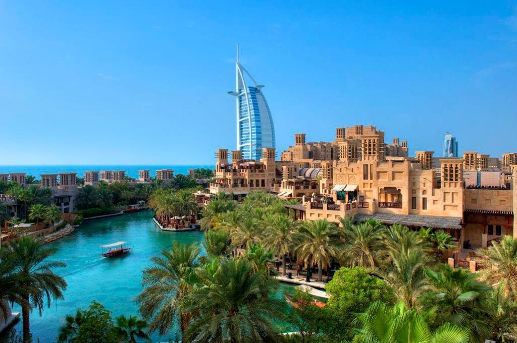 Moderne arkitektur knejser højt over palmer og klart blåt vand.