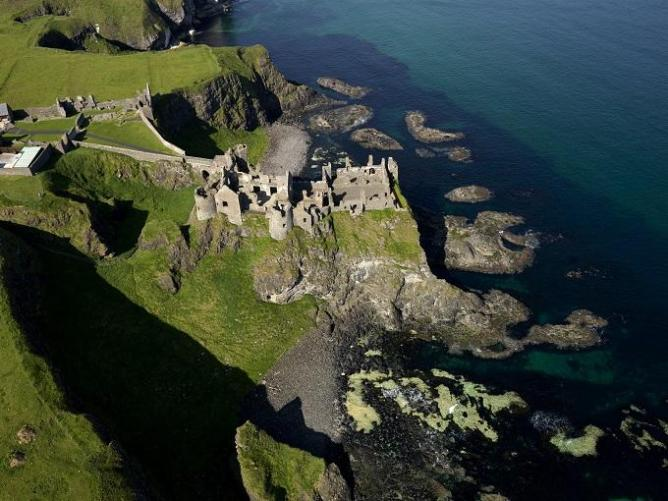Aerial view of the medieval Dunluce Castle perched on a cliff overlooking the ocean