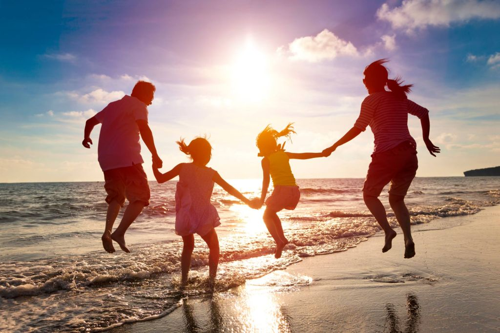 Family jumping for joy at the beach