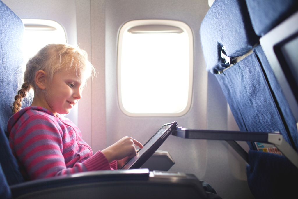 Girl with a tablet on a plane