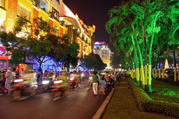 Travl gade i Ho Chi Minh. Neonlys, scootere. Mennesker der går. Oplyste huse og palmer.
