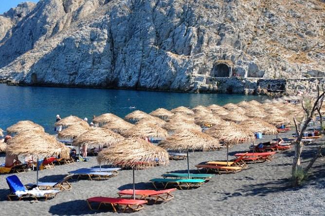 Ψάθινες ομπρέλες και ξαπλώστρες με θέα τα βράχια σε παραλία στη Σαντορίνη