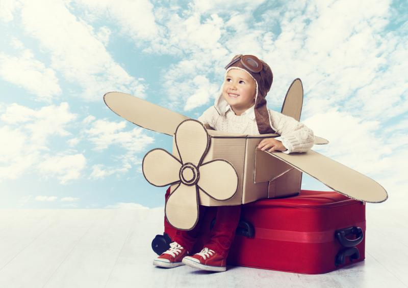 A smiling child wearing a plane made out of cardboard