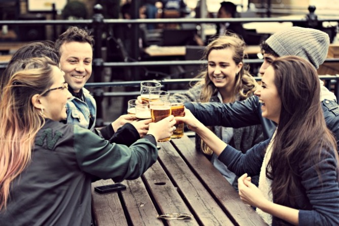 "Friends ""cheers-ing"" pints at an outdoor pub patio in London. Tips for Saving Money While Travelling - Euro Trip 
