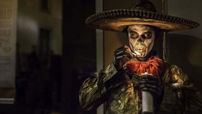 A man dressed in Day of the Dead costume, with skeleton makeup on his hands and face, a large sombrero. Blowing out a match after lighting a candle. Day of the Dead in Mexico / Skyscanner Canada