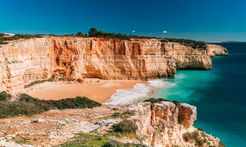 Ψηλά βράχια πλαισιώνουν μια αμμουδιά στο Αλγκάρβε