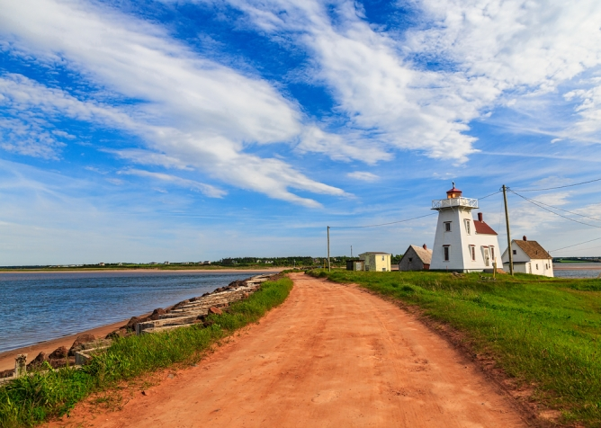 sandy red road beside a lighthouse and water in Prince Edward Island