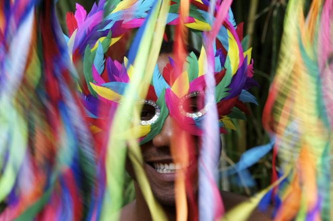 Καρναβαλιστής με πολύχρωμη μεταμφίεση διασκεδάζει