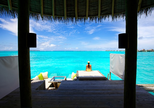 girl sitting out on a dock facing the ocean in the Maldives
