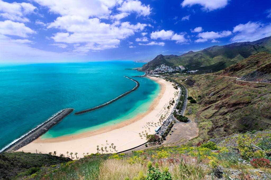 Aflang sandstrand og klart blåt hav. Bag stranden græs, blomster på bakker. I baggrunden mørke bjerge.