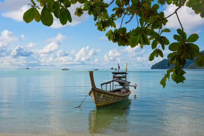 a boat docked on the ocean shore in Thailand, one of the popular countries in Asia to visit with some of the best flight deals