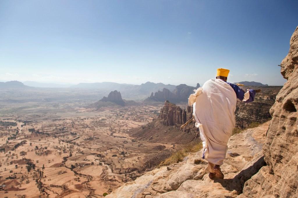 a man walking along a mountain ridge in Ethiopia