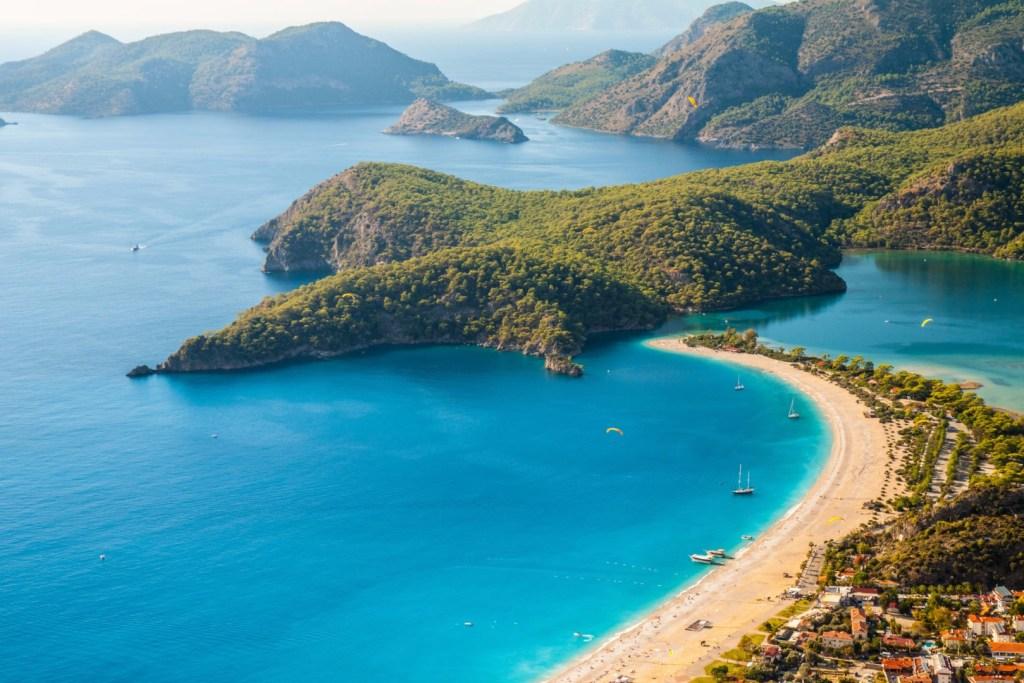 Kurvet strand, gyldent sand, helt klart og blåt havn