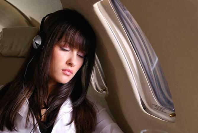 woman wearing headphone sleeping on long-haul flight