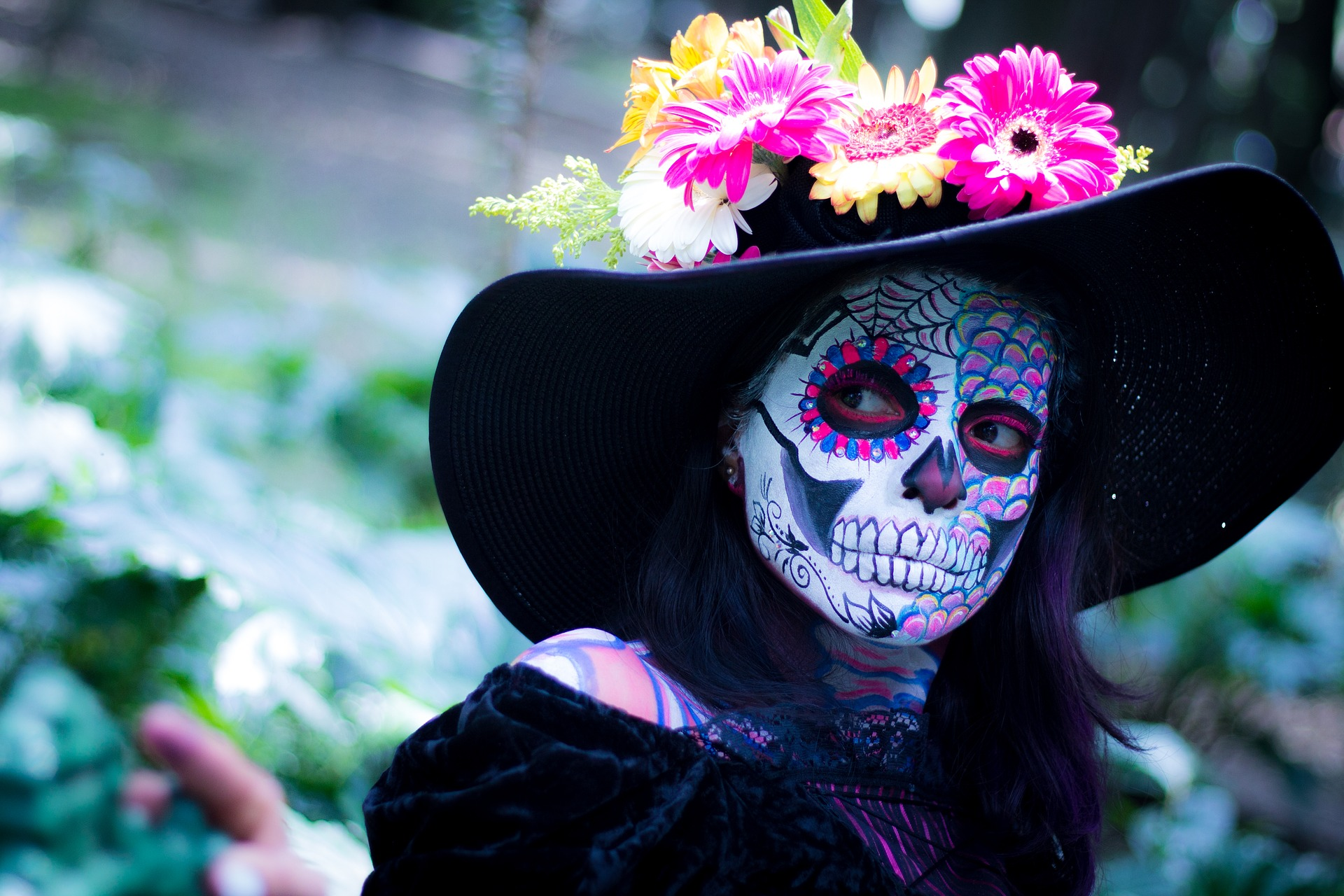 A woman in Day of the Dead costume with colourful skeleton makeup and a large black hat with orange and pink flowers on top. Day of the Dead in Mexico / Skyscanner Canada