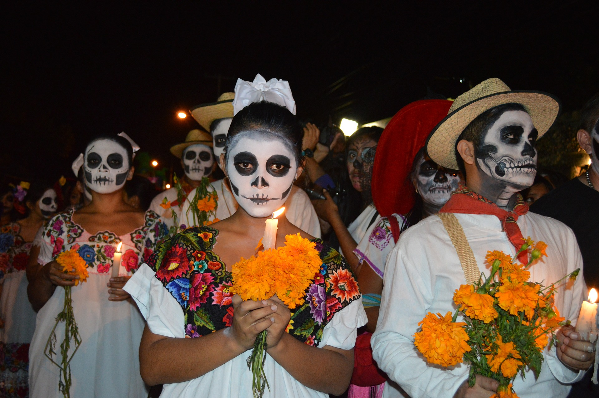 Group of people dressed in costume for Day of the Dead. Skeleton makeup and orange marigolds. Day of the Dead in Mexico / Skyscanner Canada