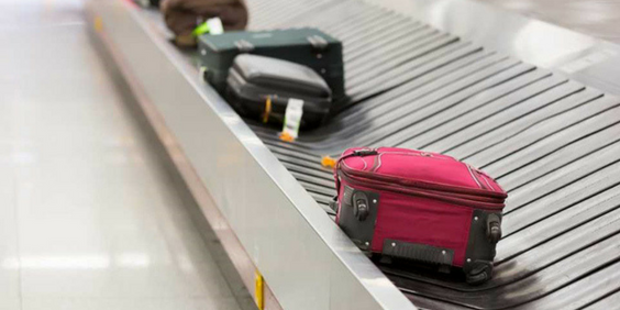 Several suitcases on a baggage claim conveyor belt. Checked Luggage and Carry-on Baggage Rules   Skyscanner Canada