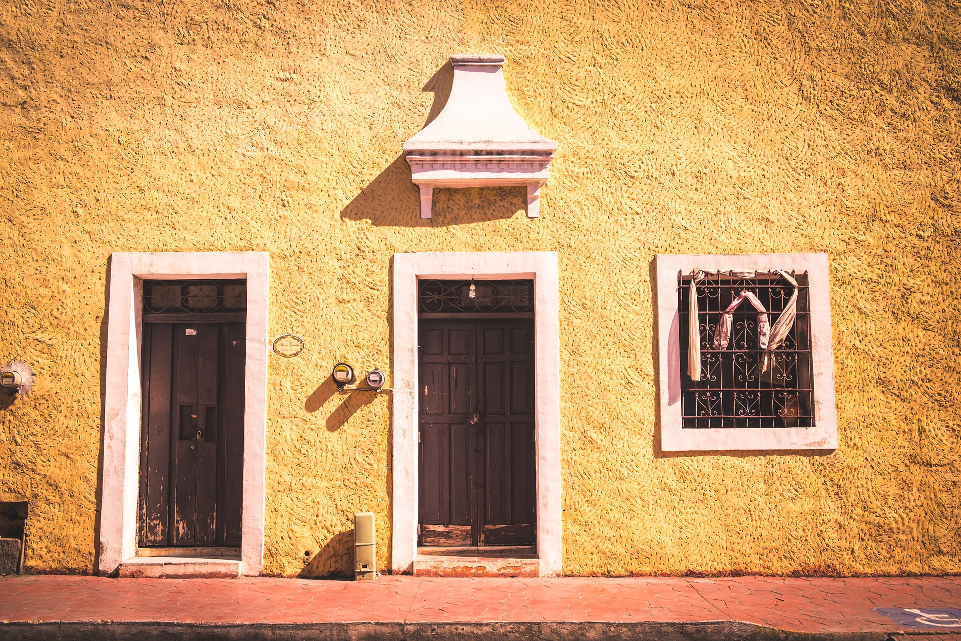 Front doors and yellow wall in Mexico. Flight deals to Mexico
