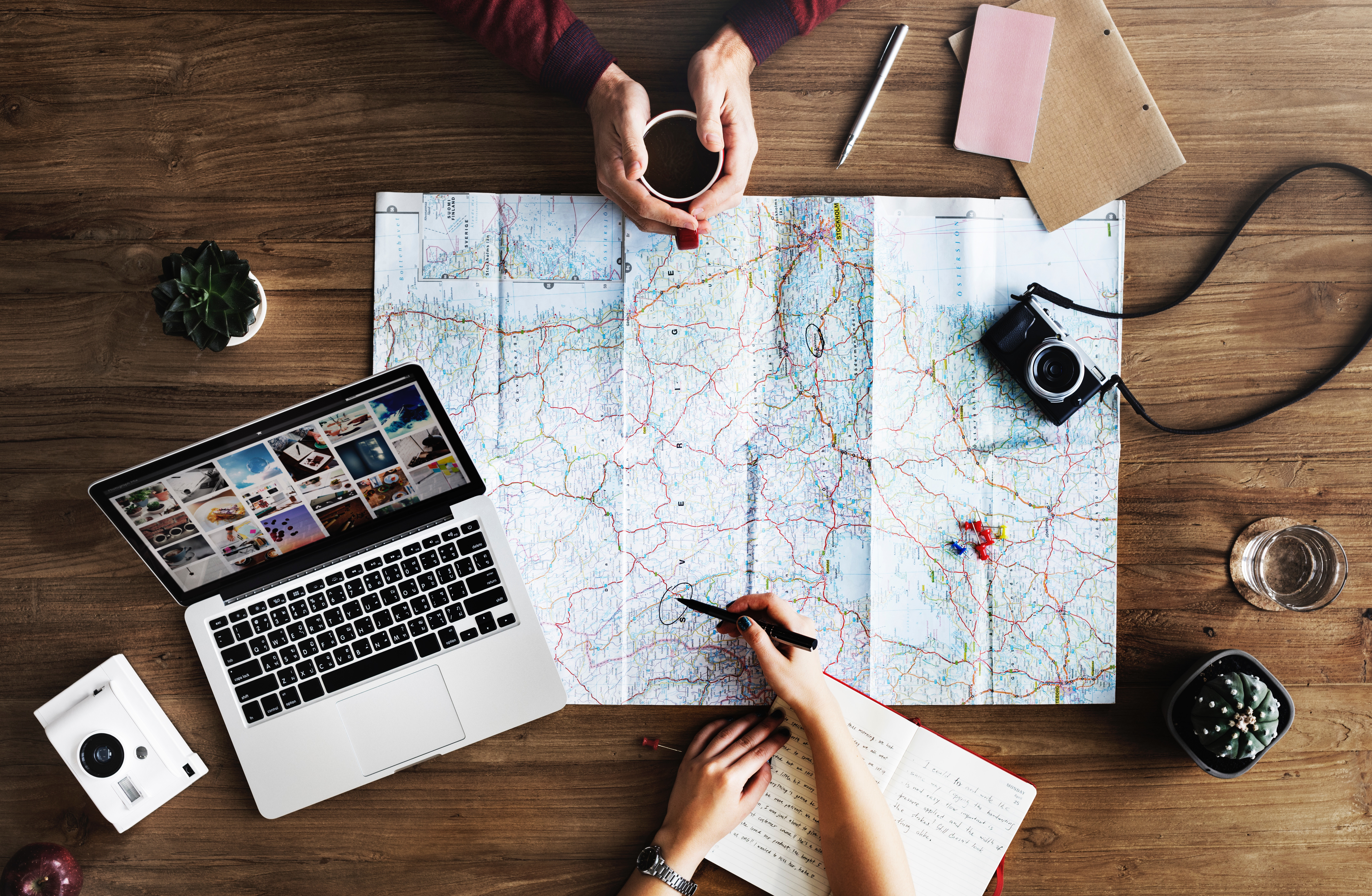 Trip planning with map, laptop and phone.