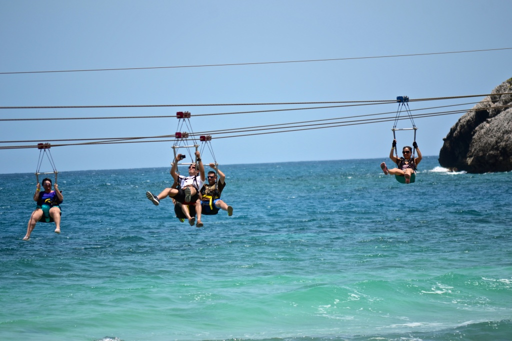 tourists zip lining over the water
