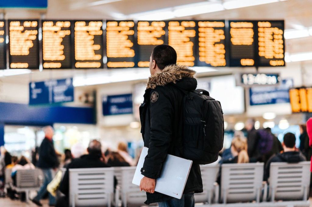 man looking at departures screen at airport with carry-on backpack