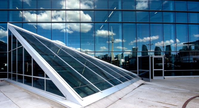 The Toronto skyline is reflected onto the glass windows of Billy Bishop Airport.