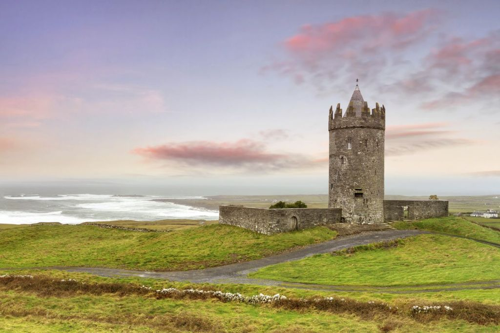Doonagore Castle in County Clare with the waves crashing in the distance