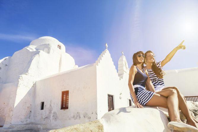 Δύο κοπέλες κάθονται μπροστά στην κατάλευκη εκκλησία της Παναγίας Παραπορτιανής στη Μύκονο