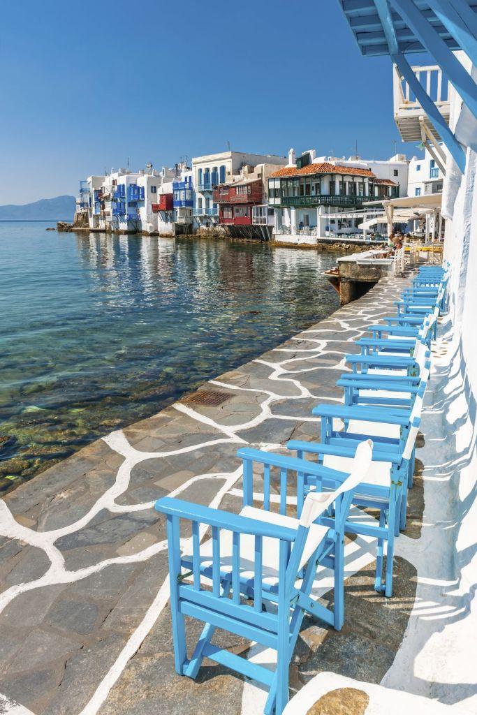 Kαρέκλες δίπλα στη θάλασσα με θέα τη γραφική Μικρή Βενετία της Μυκόνου