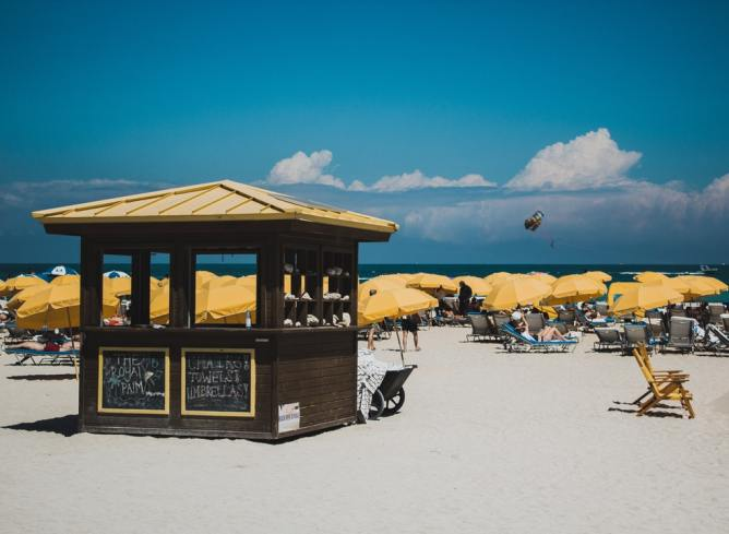 Beach hut surrounded by yellow umbrellas, Miami, Florida
