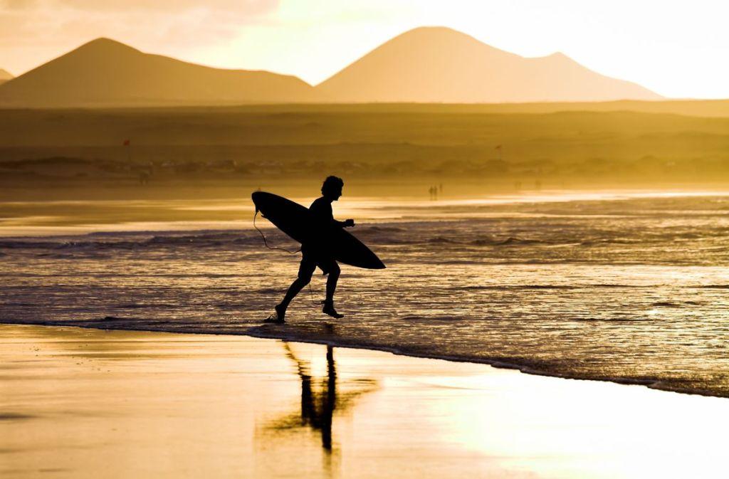 Σέρφερ μπαίνει στη θάλασσα το ηλιοβασίλεμα